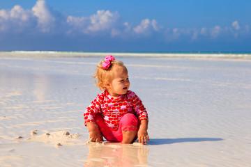cute little girl playing on summer beach