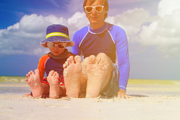 father and son feet on summer beach