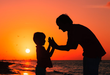 father and son playing at sunset