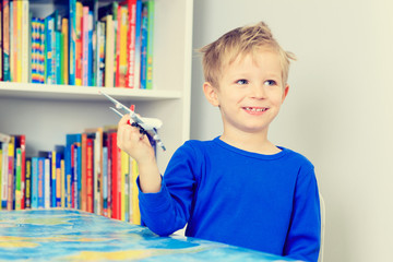 little boy playing with toy airplane flying over world map