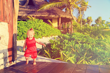 happy little girl walking in tropical resort