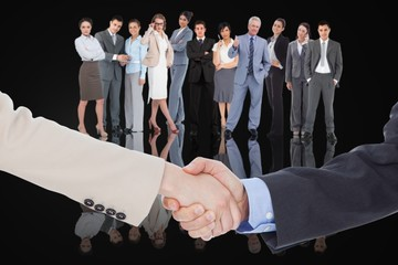 Smiling business people shaking hands while