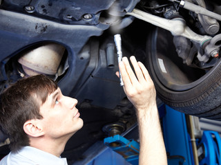 Motor mechanic inspecting the engine of a car