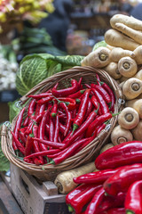 A basket of red chilies displayed on a vegetable stall