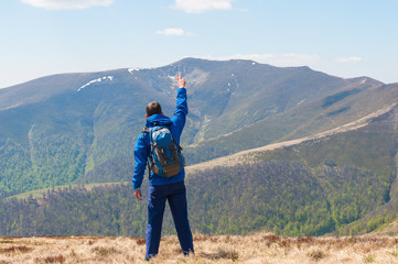 Mountaineer reaches the top of a mountain in sunny spring day.