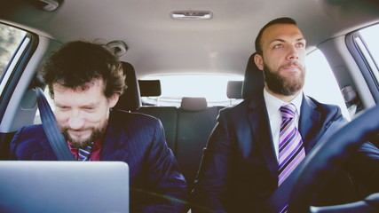 Two business men working with pc in car retro style