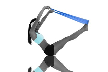 Fit young woman exercising with a blue yoga belt