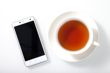 White smartphone and a cup of tea on white glass table
