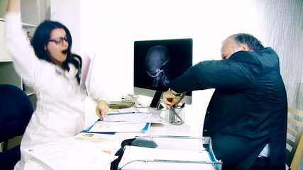 woman doctor and man dancing in office happy