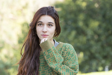 Pensive beautiful young woman with green sweater, outdoor.