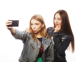 two teenagers taking picture with smartphone