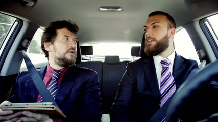 Two cool business men going to meeting driving car