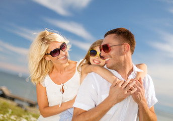 happy family in sunglasses having fun outdoors