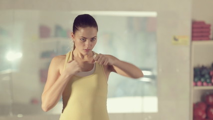 Girl in good physical shape boxing  and making workout at the