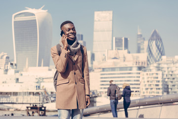 Young man talking on mobile with London city on background