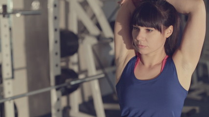 Girl in sportswear doing stretching in a fitness room among