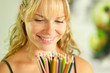 Young female artist holding colored pencils and smiling