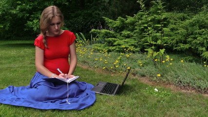 woman look for info about pregnancy in laptop, note down to book