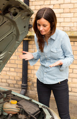 young woman looking annoyed at the engine of her car