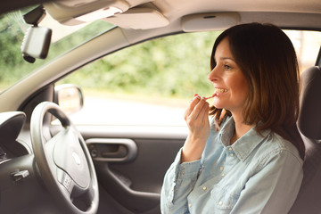 young woman applying lip gloss in her car