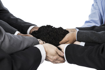 Business people holding soil in their hands