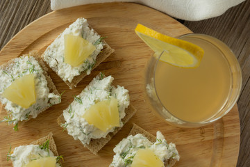 Farmer cheese sandwiches with pineapple and juice on wooden plat