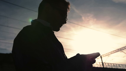 Stylish businessman using cell phone at sunny evening