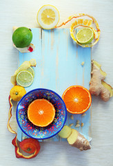 Various citrus fruits and ginger on blue cutting board