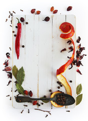 Different spices on a white wooden board