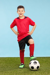 Junior in a soccer uniform standing over a soccer ball