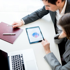 Businessman and businesswoman, analysing a statistical business