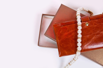 Brown women's wallet and a necklace of white pearls