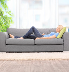 Young woman sleeping on a modern sofa at home