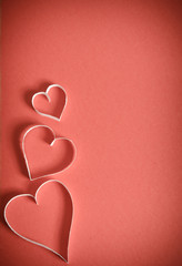 three hearts from white paper are lying on a red background