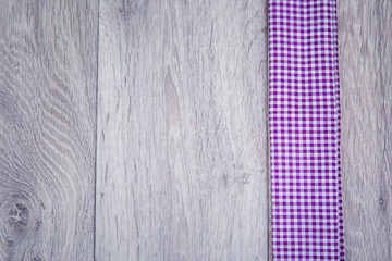 Purple checkered cloth son wooden background in rustic style