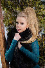 Beautiful young girl in a fur sleeveless jacket