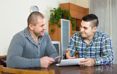 Man helping friend to fill document indoor