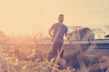 Handsome young athlete running in the park at sunset