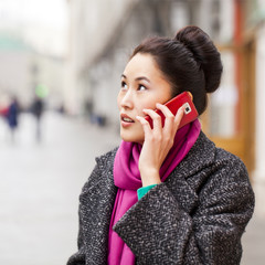 Happy beautiful asian woman calling by phone on the spring stree