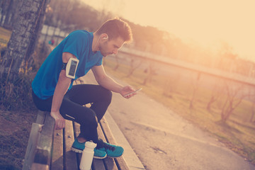 Male athlete sitting in the park at sunset with mobile phone