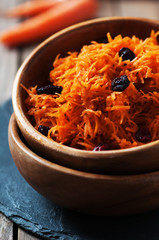 Carrot salad with raisins on the wooden table,