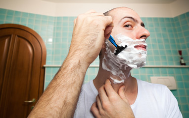 Man using a disposable razor to shave his beard off