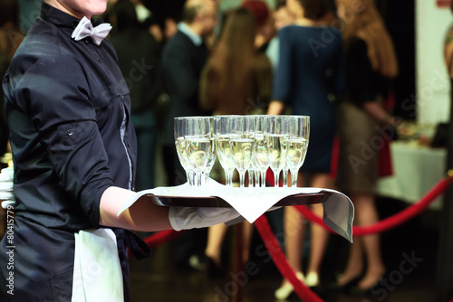 Leinwanddruck Bild Waiter with tray and wine glasses at party