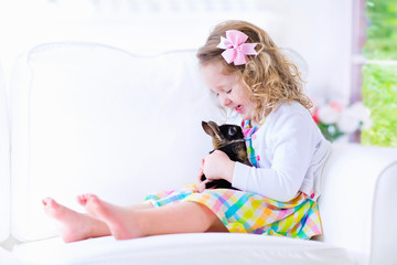 Adorable little girl playing with a rabbit