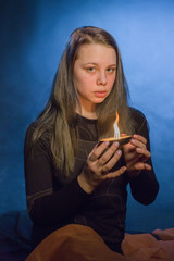 Portrait of the young woman with a candle