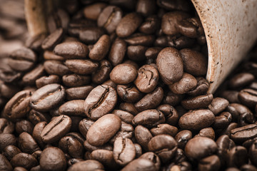 Close up of a cup spilling dark roasted coffee beans