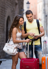 Couple with GPS navigator and baggage