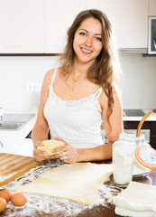 Happy young woman preparing dough