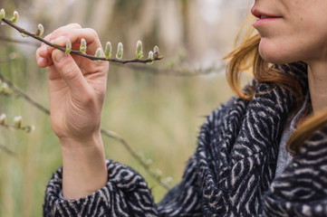Woman touching branch with buds