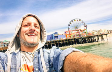 Handsome man taking a selfie at Santa Monica pier in California